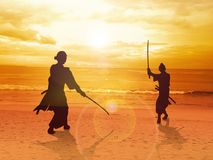 Ready For A Duel. Two Samurai in duel stance facing each other on the beach Stock Photos