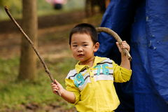 Ready for fight. A cute chinese boy playing with wood sticks as if ready for fight Stock Photos