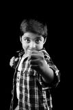 Ready for a Fight. A black & white portrait of a cute Indian boy showing his fist telling that he is ready for fight, on black studio background. Focus on the stock images