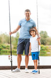 Ready for fishing. Full length of father and son holding fishing rods and smiling while standing at the riverbank together Stock Photo