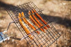 Ready-flavored Sausages on the hand-held grill in the forest royalty free stock images