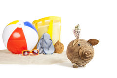 Ready for Fun Tropical Beach Vacation. Coconut Piggy bank in foreground with Colorful Beach Ball, Star Fish and Sandals, Flip Flops in Beach Sand in background Stock Photography