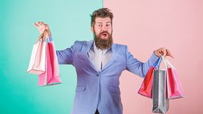 Ready for holiday. Buy gifts in advance. Enjoy shopping black friday. Hipster shopping with discount. Man bearded. Hipster businessman formal suit carry paper royalty free stock image