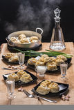 Ready hot manti on black plates, vodka in the countess and three piles on an oak table-top. In style a rustic Stock Images