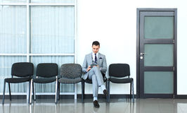 Ready for interview. Thoughtful man in formalwear holding paper while sitting at the chair in waiting room Royalty Free Stock Photos