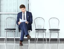 Ready for interview. Thoughtful man in formalwear holding paper. While sitting at the chair in waiting room Stock Image