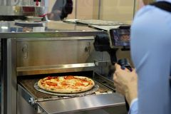 Ready Italian pizza on thin dough, fresh from the oven, production equipment. orerator shoots video production. stock image