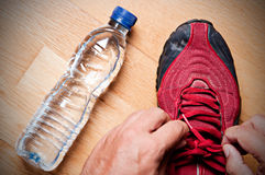 Ready for Jogging. Jogger at home, tying his sneakers with a water bottle nearby Royalty Free Stock Images