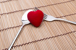 Ready for love. Red heart between silver fork and spoon on a bamboo background Royalty Free Stock Image