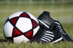 Ready for the Match. Football (soccer ball) and cleats Stock Photo