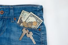 Ready money and keys to the house on a keychain are lying in a side pocket of blue jeans stock image