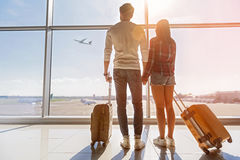 We are ready for new future. Inspired young loving couple is looking at flying plain in sky. They are standing near window at airport and holding hands Stock Images