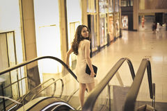Ready for the party. Pretty woman in elegant dress on the moving-stairs Royalty Free Stock Photo