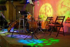 Ready for performance. Stringed musical instruments and drums on the stage Stock Images