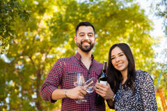 Ready for a picnic outdors. Portrait of a handsome young men with a beard carrying a couple of glasses and a bottle of wine with his girlfriend Stock Photos