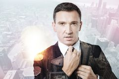 Ambitious serious man fixing his tie Stock Photo