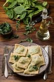 Ready ravioli in a plate, spinach, olive oil in a jar Stock Image