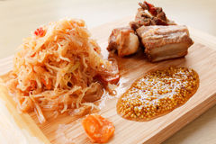 Ready roasted pork ribs with tomato, carrots and cabbage on a  cutting board Royalty Free Stock Photo