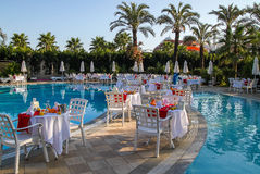 Ready romantic dinner next to the pool. Royalty Free Stock Images