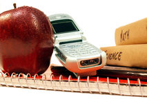 Ready for school. Pile of books, apple and cellular phone stock image
