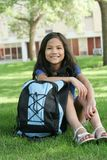 Ready for school. Eight years old girl ready for school. Backpack ready, sitting in front of school Royalty Free Stock Images
