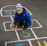 Ready for school. A little boy studying numbers on the hopscotch squares painted on the asphalt ground. The kid sitting and pointing the figure 6 on the Stock Photos