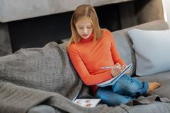 Serious intelligent girl doing home task. Ready for school. Serious nice intelligent girl sitting on the sofa and writing notes while doing her home task Stock Photo