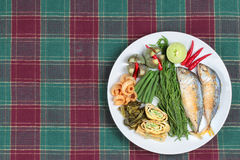 Ready side dish of deep fired mackarel,vegetable omelet,crispy pork rind,pickle lettuce,halve green lemon,red chili and boiled of Stock Images