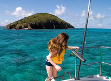 Ready for Snorkeling. A young girl on the ladder of a boat, getting ready for snorkeling in the blue waters of the Caribbean sea, St. Croix, US Virgin Islands Royalty Free Stock Photo