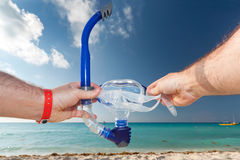 Ready for snorkeling in Caribbean Sea. Snorkel equipment in hands against beach and sky Royalty Free Stock Photography