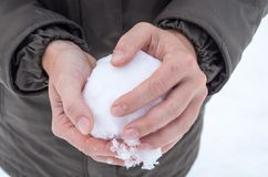 Ready for a snowball fight? Close-up of handy creating a snowball