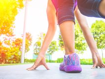 Ready steady go. Closeup of running shoes on grass,. Young lady on start position and going to run in park stock image