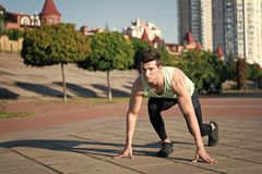 Ready steady go. Healthy lifestyle concept. Man runner at starting position. Athlete on asphalt path on sunny summer day outdoors. Fit macho in track suit and royalty free stock image