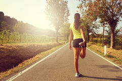 Ready for success. Female figure stretching goes to win. Woman runner road jogging clothes flare sunset street fitness cross Stock Photo
