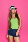 Ready For Summer Sun. Smiling young beautiful woman in jeans shorts and lime green shirt posing in green sun visor cap. Three quarter length studio shot on pink Royalty Free Stock Photography