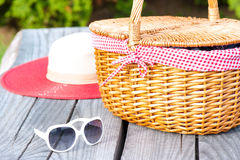 Ready for summer weekend. Sunglasses hat and wicker basket. Royalty Free Stock Photography