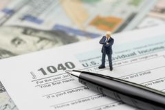 Ready for tax submission period concept, miniature people success confident businessman standing with pen on 1040 US individual. Income tax filling form with US royalty free stock images
