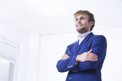 Ready to achieve everything. Handsome businessman in a blue suit posing in a light office Stock Photo