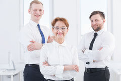 Ready to achieve success. Confident mature women boss and two content office workers standing in light interior Royalty Free Stock Images