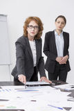 Ready to achieve success. Two women during business presentation, standing beside desk, light interior Royalty Free Stock Photo