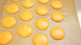 Ready-to-bake macaroons are on parchment for baking. Shadow of sunlight on parchment paper. Preparation for the holiday. Preparation for Christmas, New Year stock footage