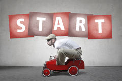 Ready to begin. Man driving a small, red toy car Stock Image