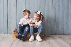 Ready to big travel. Happy little girl and boy reading interesting book carrying a big briefcase and smiling. Travel royalty free stock images
