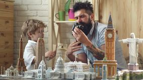 Ready to big travel. Little child and man with binocular and miniature architecture. Boy son and father with world. Landmark buildings in miniature. Discovering stock video footage
