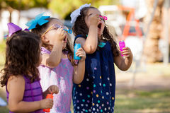 Ready to blow some bubbles. Very competitive little girls trying to make more bubbles than their friends Stock Photography