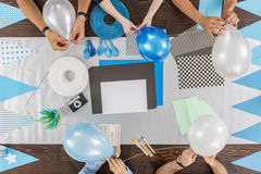Ready to celebrate special event. Group of friends sitting together at the table and preparing the party decorations Stock Image