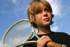 Ready to compete. Closeup of boy playing tennis against a blue sky Royalty Free Stock Photography