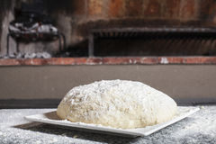 Ready to cook. A raw dough pizza ready to cook in a barbacue Royalty Free Stock Photography