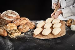 Ready to cook bread dough on a wooden paddle. Ready to cook loaves of bread dough on a wooden paddle held by a chef over a counter with display of assorted royalty free stock photography