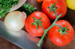Ready to cook tomatoes and vegetables. Fresh vegetables in a cutting board ready to be cut Stock Photography